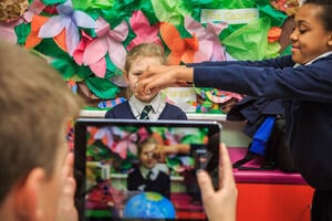 A group of three children. A girl sits as another stands to her left sprinkling paper in front of her face onto a globe. A boy is filming this on a tablet device. The background wall is decorated with colourful paper leaves and the word 'forest'.