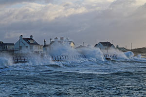 The picture shows a stormy sea, with waves whipping up over the sea wall onto the promenade.