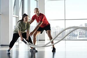 A woman training with ropes whilst a man supports and views her form