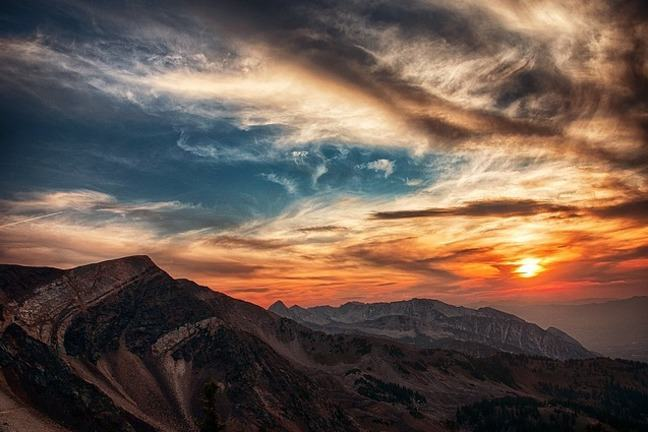 Landscape of rugged mountain ranges and the sun appearing through the clouds at dusk