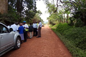 A rural road in Uganda with a hard mud surface. A vehicle is parked and a group of smartly dressed people appear to be in conversation. Some have papers, high visibility vests and hard hats.