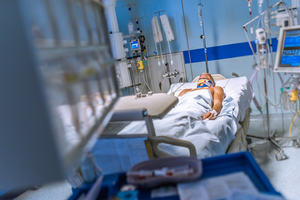 A patient in a hospital bed, connected to various machines