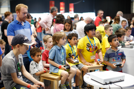 A group of boys, some wearing CoderDojo t-shirts, form a semi-circle and are holding controllers, looking at something out of frame. In the background there is a crowd including young people using laptops.