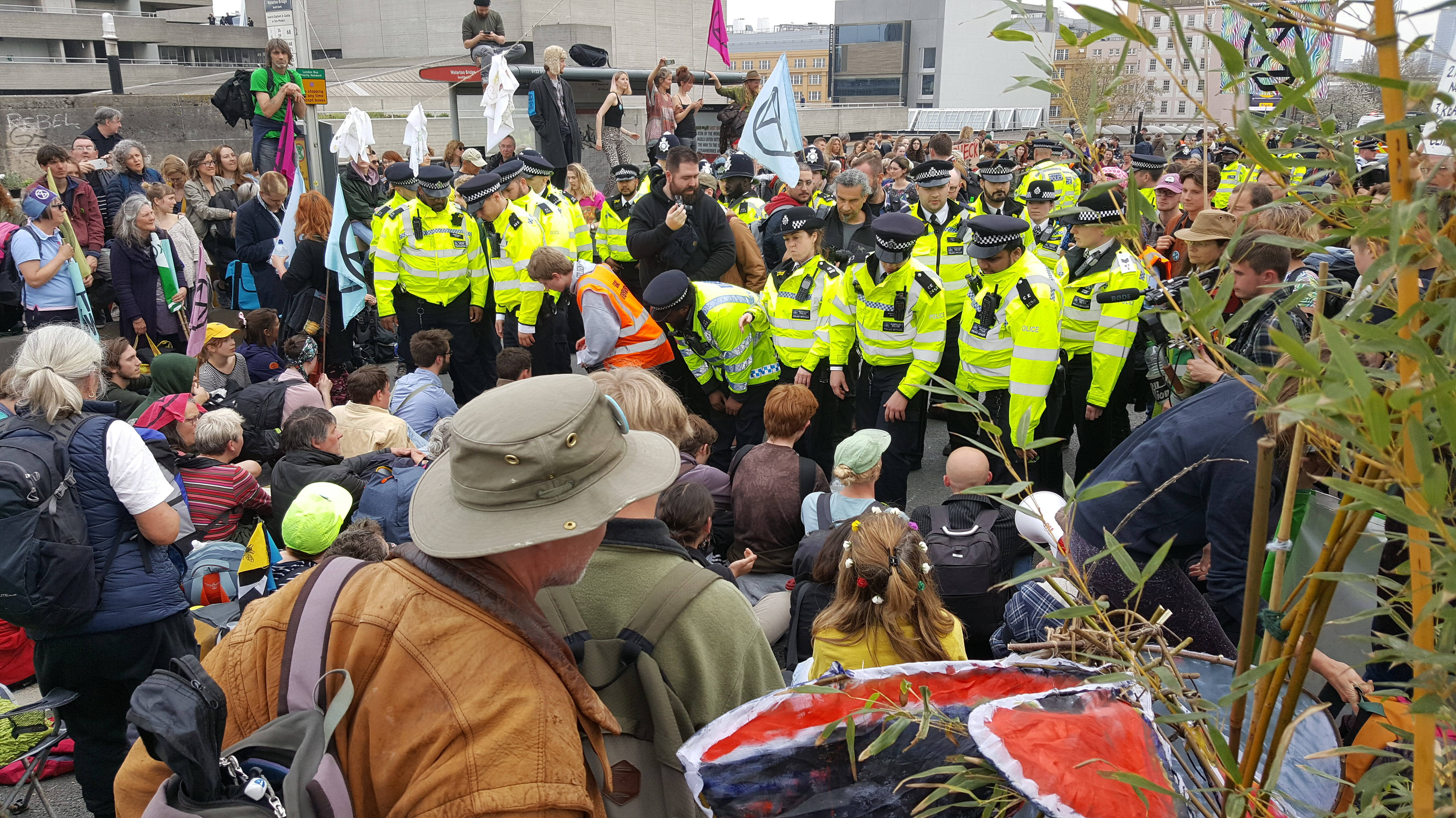 A line of police face a crowd of protestors sat on the ground.