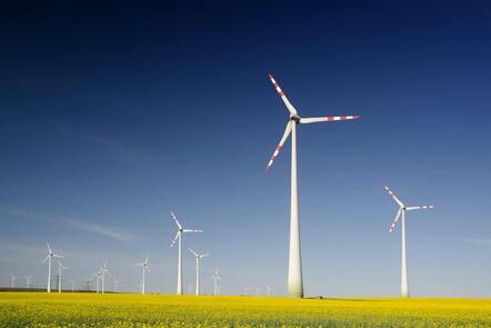 A wind farm with tall wind turbines in a grassy field.