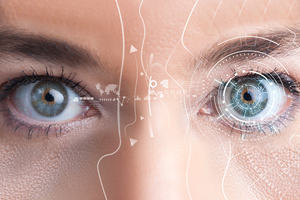 A woman's eye containing a reflection of computer graphics.