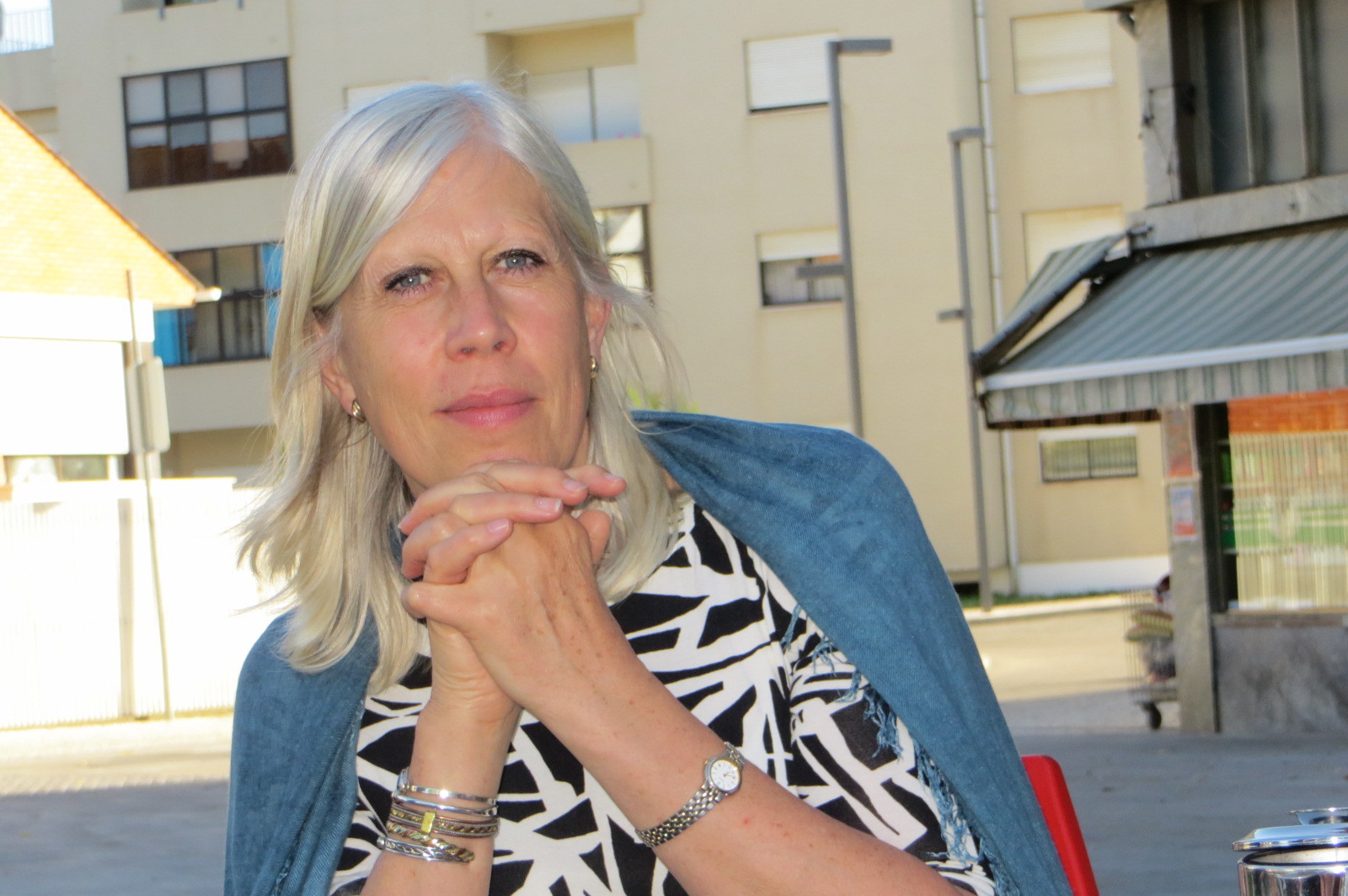 A profile picture of a woman with white hair, wearing a blue cardigan