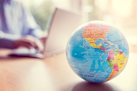 Person sitting at counter using laptop in background out of focus with small globe sitting on counter in foreground.
