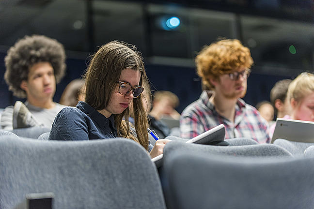 Student writing notes in a lecture