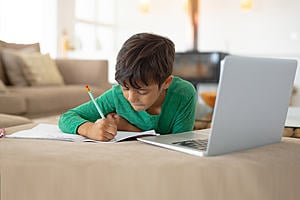A young learner, studying in front of a laptop