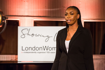 A headshot of Ebinehita Iyere wearing a black blazer and speaking at an event