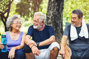 Three happy looking older people talking and resting after exercising