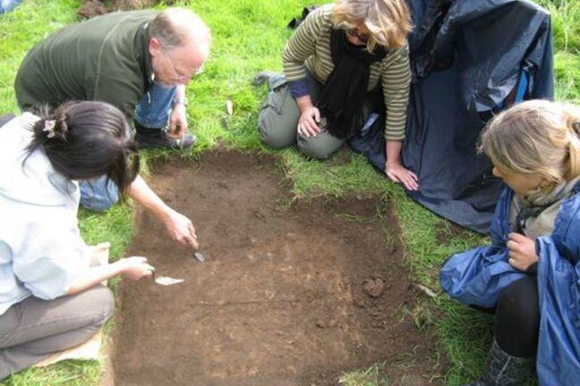 Several people trowelling back a section of the ground from which the turf has been removed. They are revealing the outline of a grave cut.