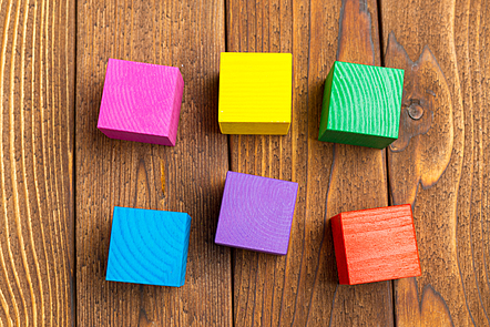 Six toy blocks, each one a different bright colour.