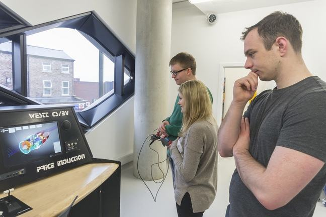 Students look at an engine simulation on a computer screen