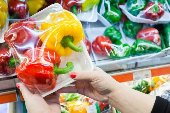 Hands holding a package of three peppers, two red, one yellow, on a white tray with plastic wrap, with similar packages in the background.