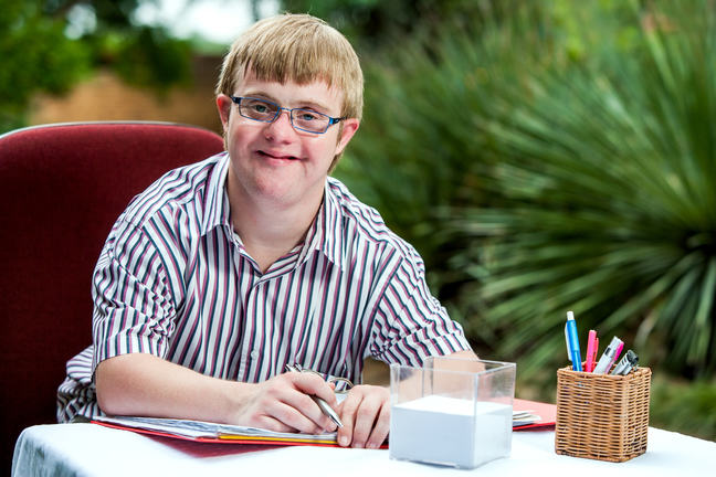 A person with an intellectual disability with a folder of papers.