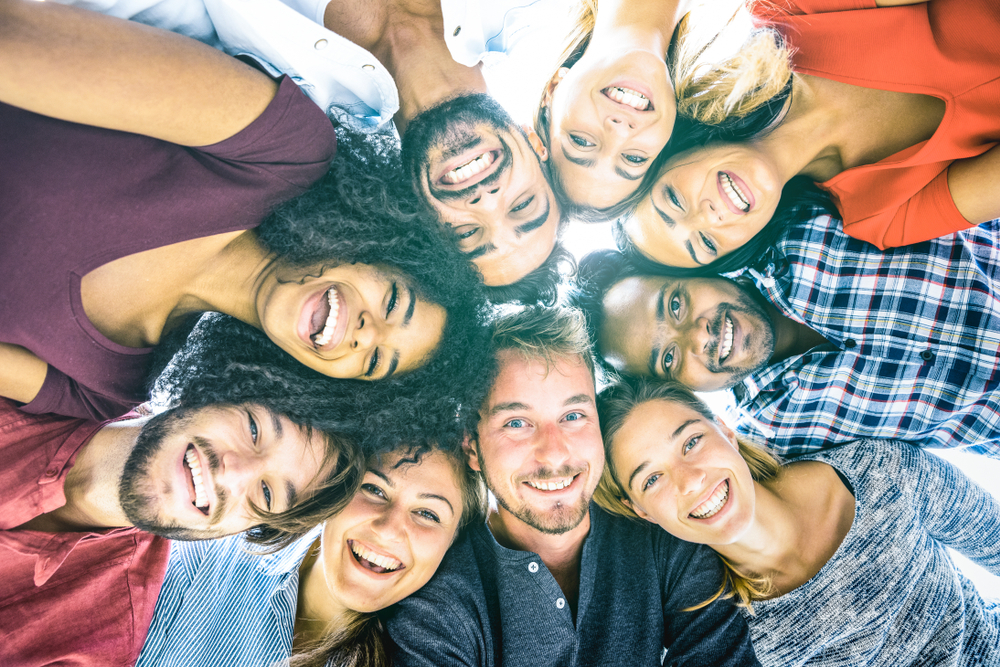 This image shows a group of young people from different cultures in a circle with their arms around each other, looking down at the camera.