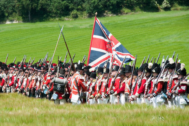 Units of the Guards in the British army practise their drill, assembled in line in a field. The Union Jack flag flies above them.