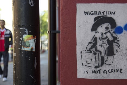 Graffiti in Bristol of Paddington bear, with the slogan 'migration is not a crime'.