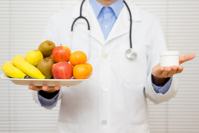 Doctor with fruit in one hand and medicine in the other.