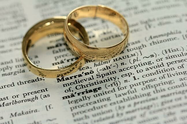 A pair of gold wedding rings placed on top of one another so they interlink. They are on top of a dictionary and the definition of 'marriage' is in focus, almost visible.