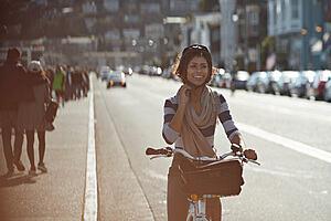 Se observa una mujer joven andando en bicicleta por la calle. Lleva casco y está sonriendo. De fondo, se observan autos circulando por la calle y personas caminando por la vereda..
