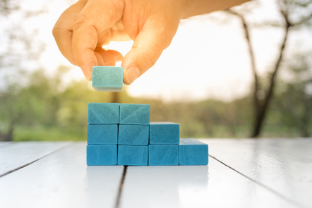 Man's hand holding blue wooden block. It is being added to a stack of blocks like a stairs on a white wooden table.