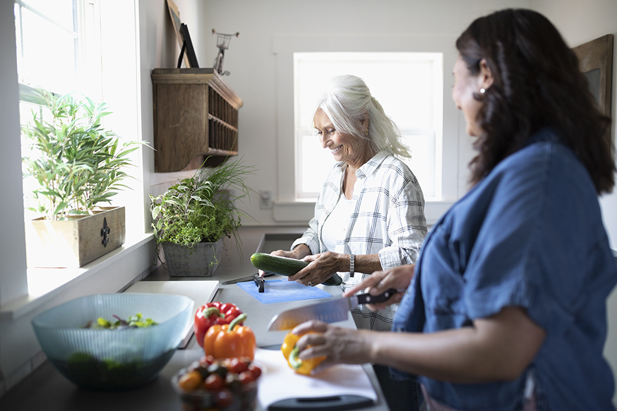 Daughter and senior mother cooking, cutting vegetables in kitchen