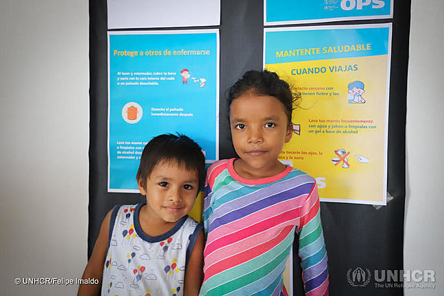 Young boy and girl smiling at the camera in front of signs explaining hygiene.