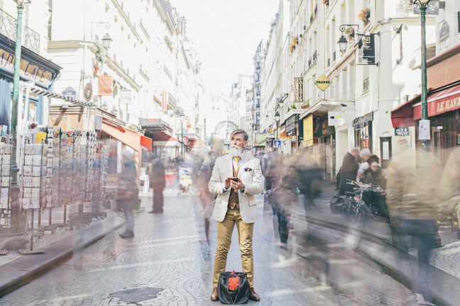 Double exposed shot of a mid-aged hipster man in a suit, standing with a mobile in hand in the middle of a busy European street.