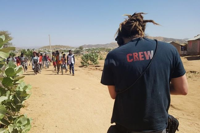 A man is visible from behind in the front of the photo. He is wearing a tshirt with CREW written on the back and has headphones on his head and carries equipment bags around his waist. He is looking towards a group of people walking along a dusty road.