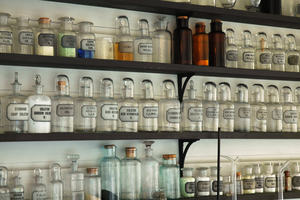 Clear old fashioned labelled bottles on a shelf in a pharmacy