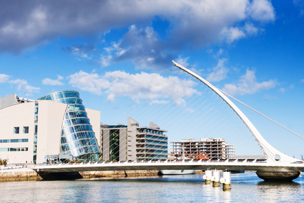 Dublin's 'Beckett Bridge' can be seen crossing the river Liffey. It is white metal with a large white curved support reaches upwards with cables attached back to the horizontal bridge, which gives it the look of a harp.