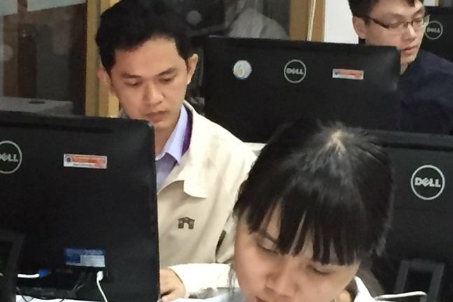 Three learners at their computers in an Information Technology room. The tilted down head of a woman in the foreground with two men facing forwards and the back of their and one other computer monitor.