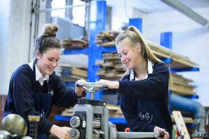 Two girls using machinery in a workshop