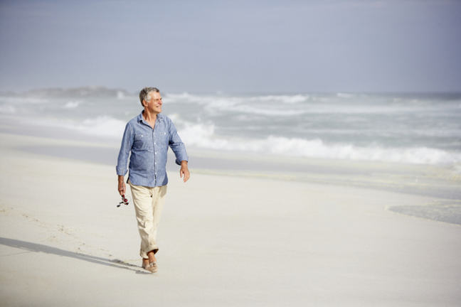 A middle aged man walking down a sunny beach smiling and looking into the distance.
