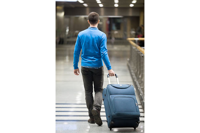 Photo of a man from behind, he's walking in an airport while pulling his luggage Behind him