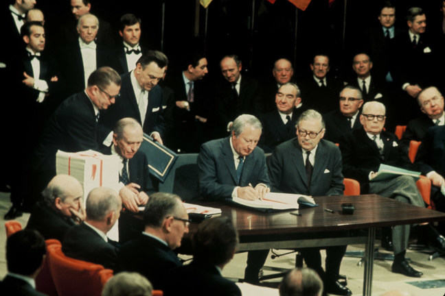 UK Prime Minister Edward Heath signs the UK's accession treaty to the EEC at a table surrounded by other men