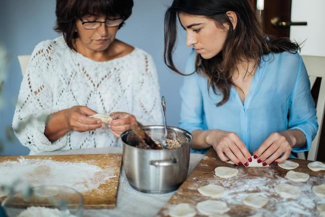 Two women making dumplings. The young person is watching what the older person does.