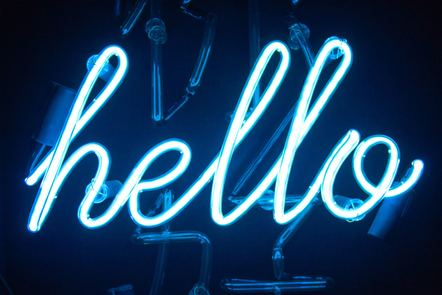 A photograph of an illuminated sign in a darkened window. The sign says 'hello' in lower case, white, cursive-style flexible tubing.