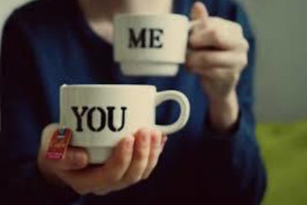 Two cups, labelled 'me' and 'you', held by a person in a blue top.  No face is visible, the hand holding the 'you' cup is extended towards the viewer.