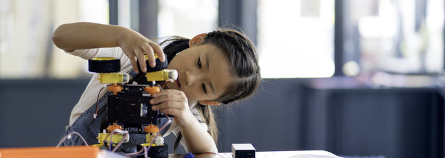 A young girl tilts her head to one side as she works on building a small robot.