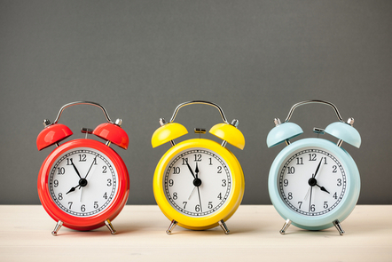 Three colourful clocks in a row next to each other.