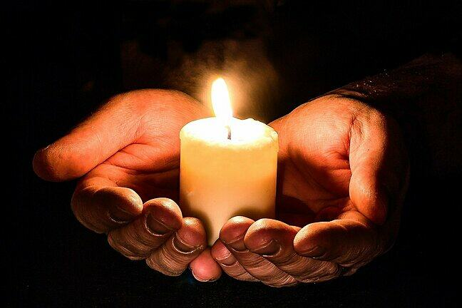 Photo of hands holding a candle
