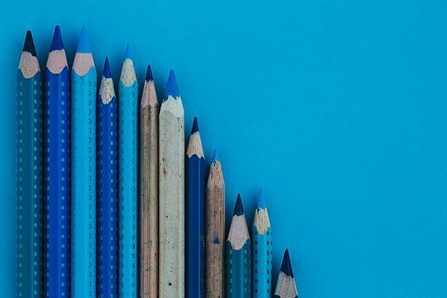 Selection of different length and different tone blue colouring pencils on a blue background