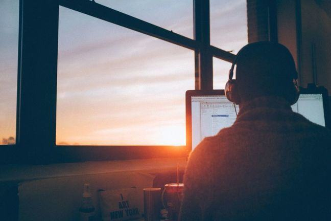 Man using computer during sunrise