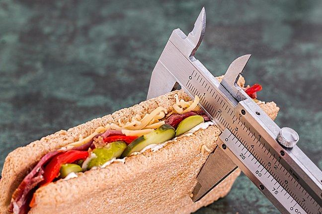 Photograph of the width of a sandwich containing cheese, tomato, ham and cucumber being measured by a caliper