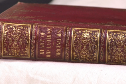 View of the decorated spine and front cover of the Heart of Midlothian original manuscript, laid on a white cloth