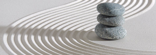 Sand with Zen-style rake patterns and a stack of small stones.